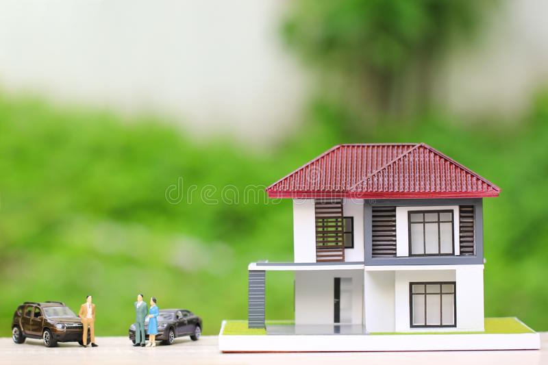 New home and Real estate trading concepts, Wooden house with Miniature people standing and car on natural green background.  stock photo