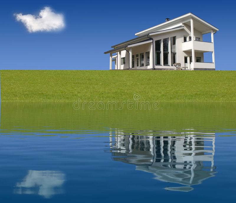 New house. Image of an house. New house for sale near lake. Hoouse reflection in the lake. Alone cloud on blue sky