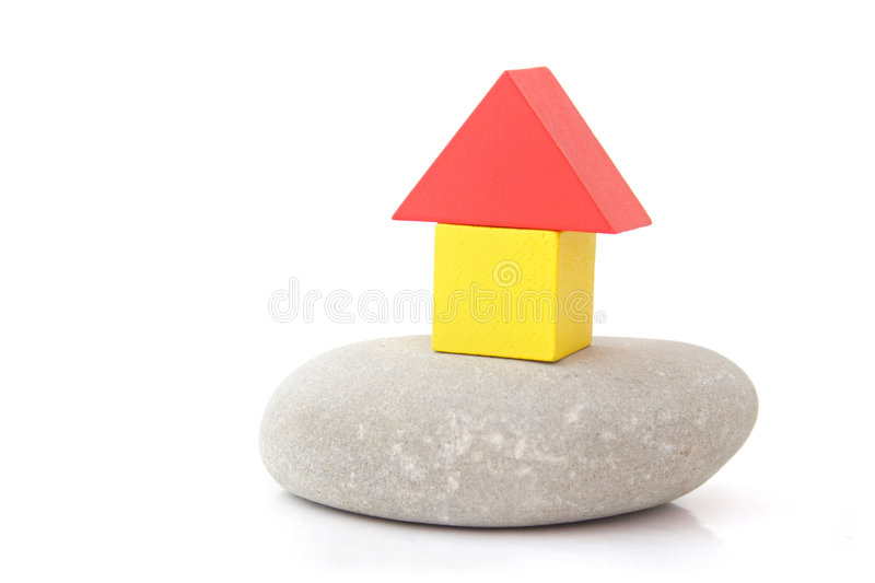 New house. A stylized house out of colorful blocks on a natural stone. All isolated on white background stock photo