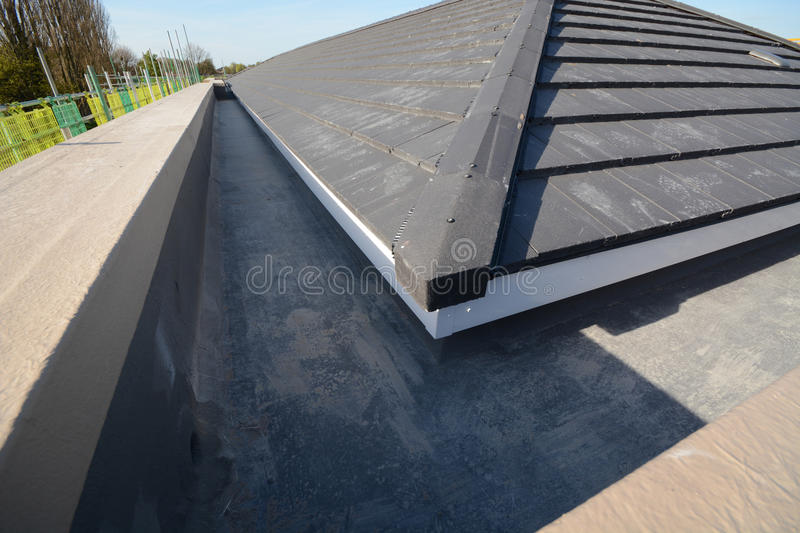 New house roofing for building construction. New tiled roof on building construction site where new homes are being built showing construction methods stock image