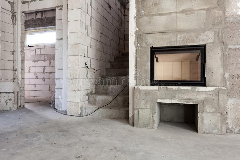 New house under construction. Modern wood-fired fireplace construction. Aerated concrete blocks, cement brickwork walls, plastic w stock image