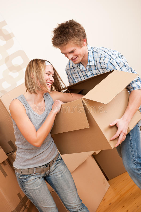 New house: Young couple moving box, unpacking. In new home stock photo