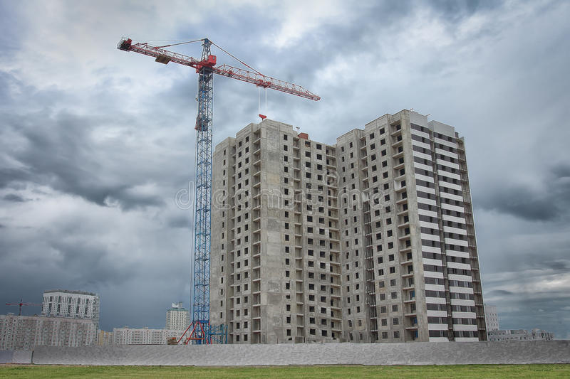 New housing on the construction site with an industrial crane. Construction of a multi-apartment residential building royalty free stock photography