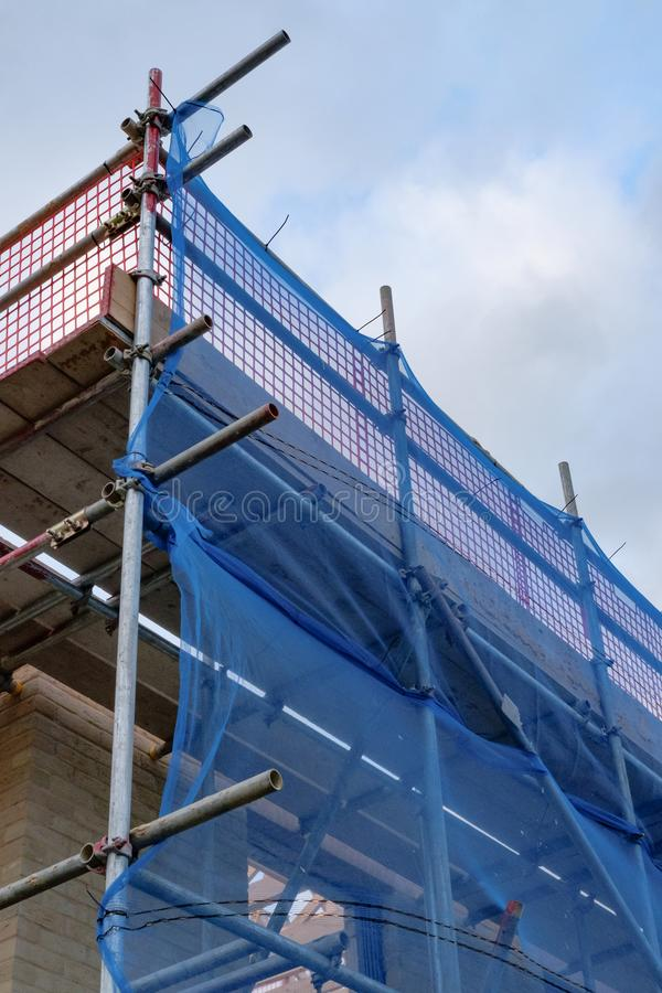 New housing development showing scaffholding and safety neeting. New residential homes being built in east Anglia, UK. The view shows safety nets, barriers on stock photo