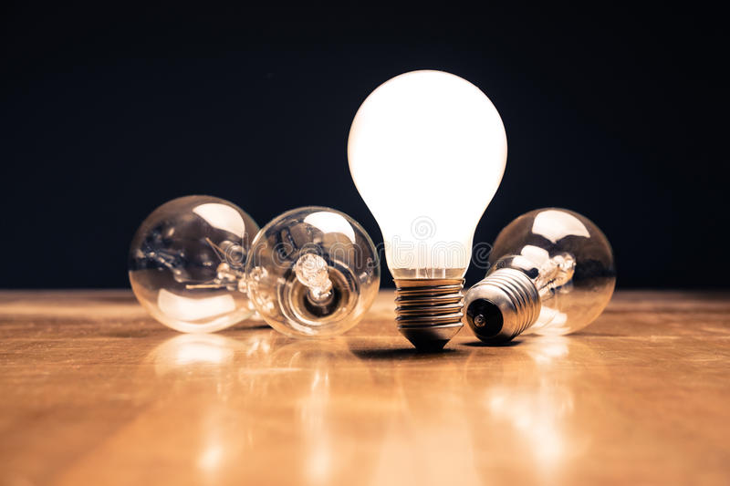 New Idea. Comparative white light bulb standing on the table royalty free stock images