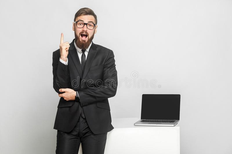 New idea! Portrait of handsome suprised bearded young businessman in black suit are standing near his working place and showing stock image