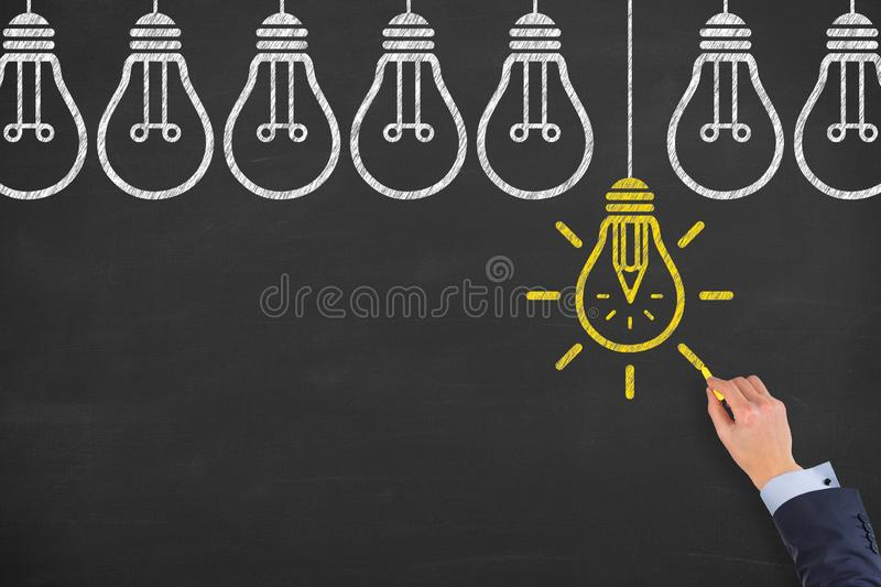 New idea solution concepts with light bulbs on a chalkboard background royalty free stock photography