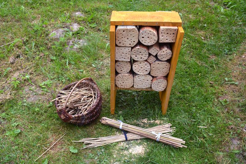 New Insect hotel and reeds in basket in garden. On grass stock images
