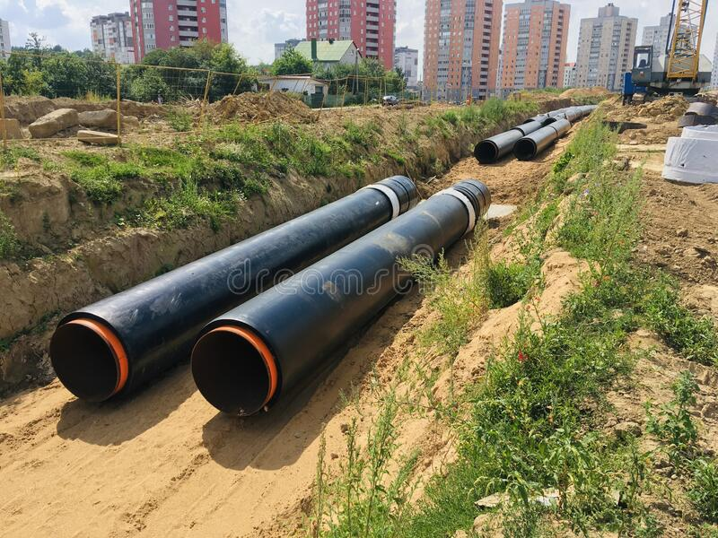 New insulated water pipes in the trench construction site stock photography