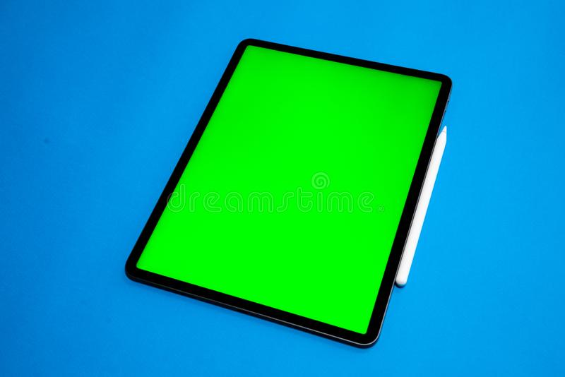IPad and iPhone, new tablet on a Blue background with a pen, and green screen top view stock images