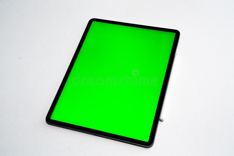IPad and iPhone, new tablet on a white background with a pen, and green screen top view royalty free stock photography