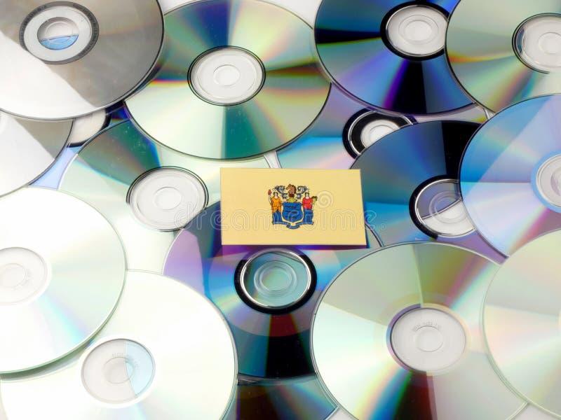 New-Jersey Flagge auf den CD- und DVD-Stapel lokalisiert auf Weiß lizenzfreies stockfoto