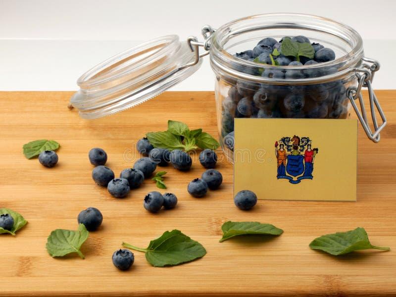 New-Jersey Flagge auf einer hölzernen Planke mit Blaubeeren auf w lizenzfreie stockfotos