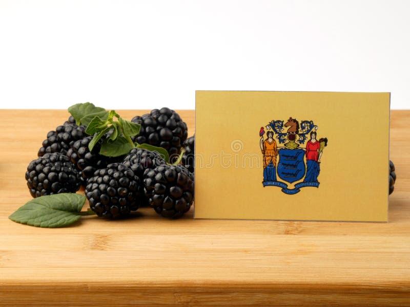 New-Jersey Flagge auf einer Holzverkleidung mit den Brombeeren an lokalisiert lizenzfreie stockfotos
