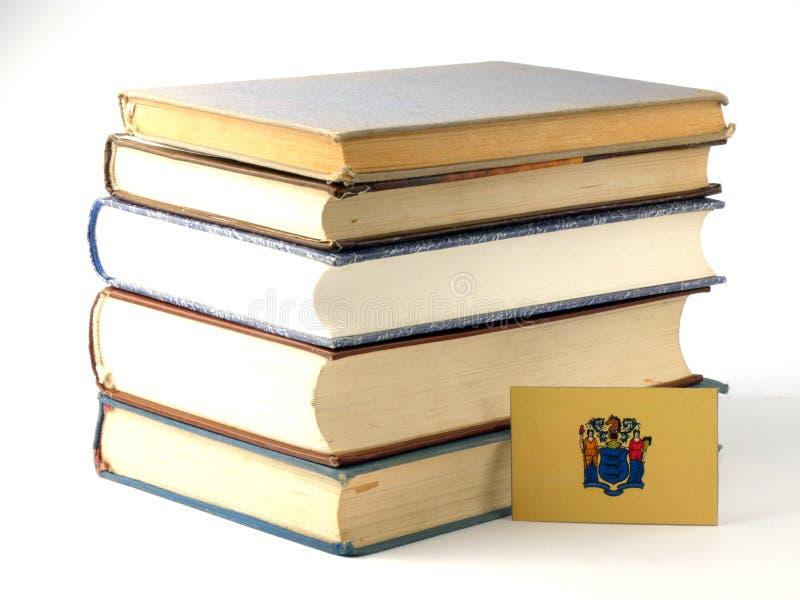 New-Jersey Flagge mit Stapel von Büchern auf weißem Hintergrund stockbild