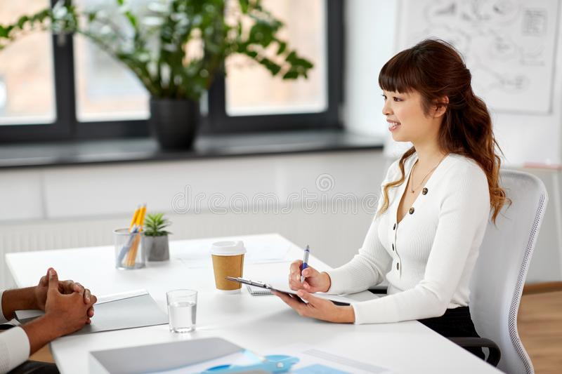 Employer having interview with employee at office stock image