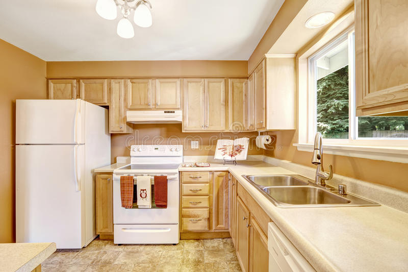 New kitchen cabinets with white appliances. New wooden kitchen cabinets in light tones with white appliances stock image