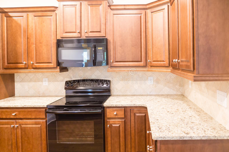 New Kitchen with Granite Countertops and Black Appliances. A New Kitchen with Granite Countertops and Black Appliances with wood cabinetry royalty free stock photos