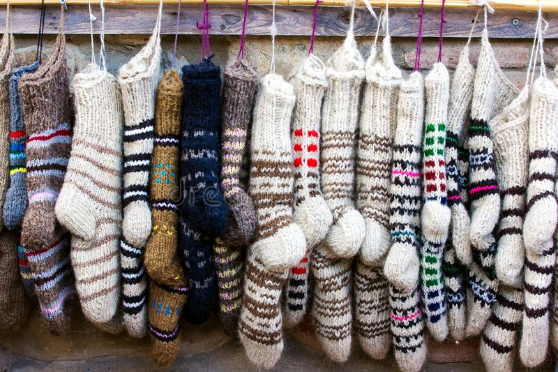 New knitted wool socks of different colors and ornaments hanging in a row.  stock photography