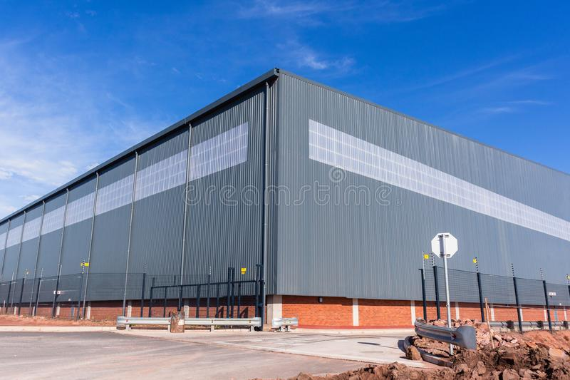 New Large Warehouse Building. New large warehouse industrial building structure in blue morning sky stock image
