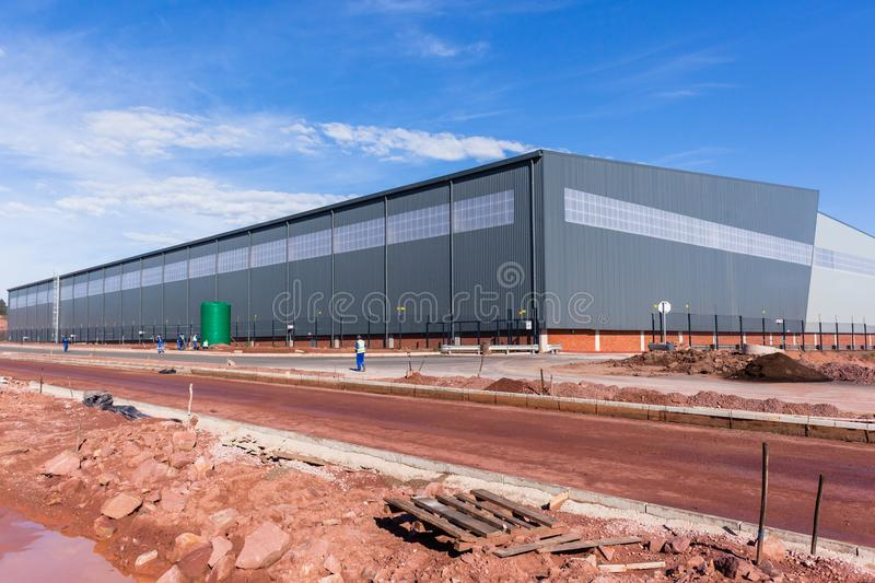 New Large Warehouse Building. New large warehouse industrial building construction structure and new roads in blue morning sky stock photography