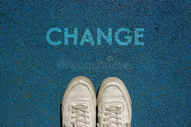 New Life Concept, Motivational Slogan with Word CHANGE on the Ground of Walk Way. New life concept, Sport shoes and the word CHANGE written on blue walk way stock images