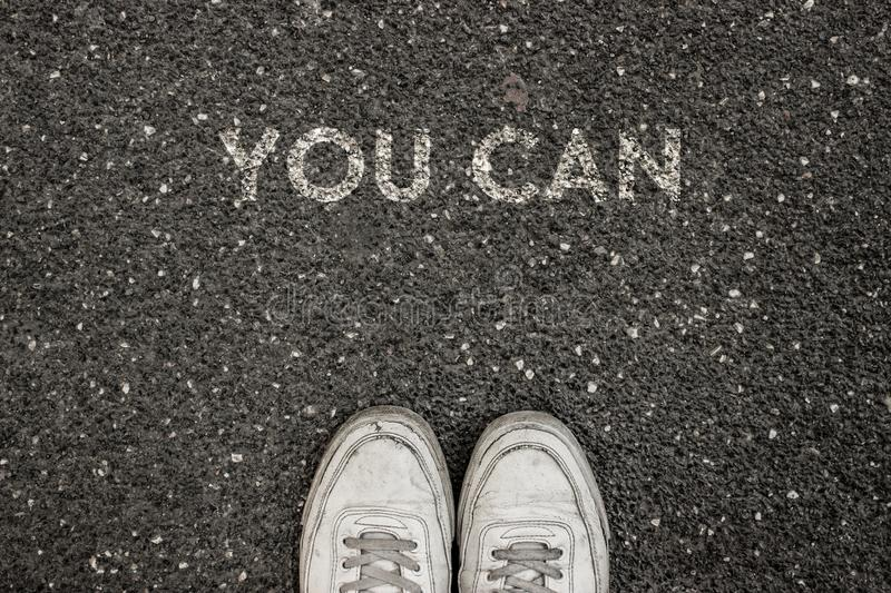 New Life Concept, Motivational Slogan with Word YOU CAN on the ground of asphalt stock image