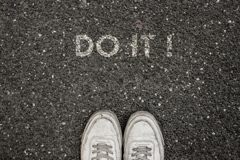 New Life Concept, Motivational Slogan with Word DO IT ! on the ground of asphalt stock photo