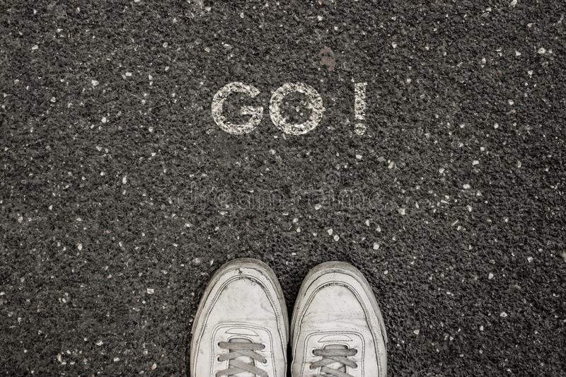 New Life Concept, Motivational Slogan with Word GO ! on the ground of asphalt stock photo