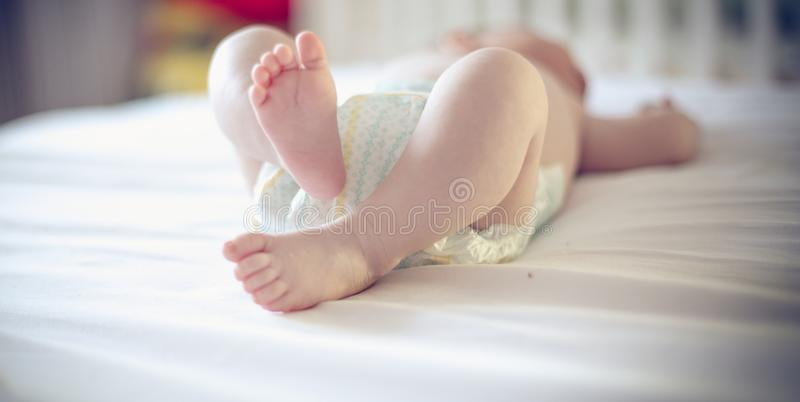 New life. Small and cute baby feet on bed. Close up. Space for copy royalty free stock photos