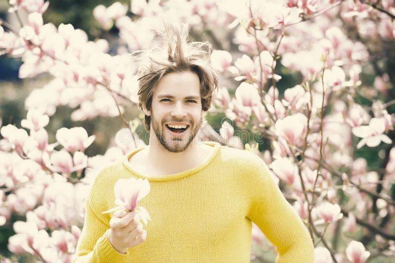 New life and optimism. Flourishing and growth. Happy man holding magnolia flower in park with blossoming trees. Spring season concept. Macho with beard smiling stock photo