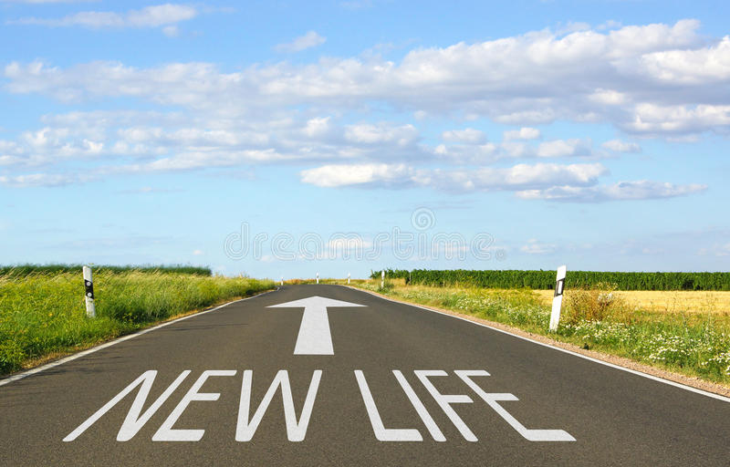 New Life - street with arrow and text. Blue sky with some clouds in the background royalty free stock image