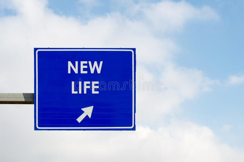 New Life words displayed on blue road sign. Blue road sign displaying New Life words on blue sky and white clouds background stock images