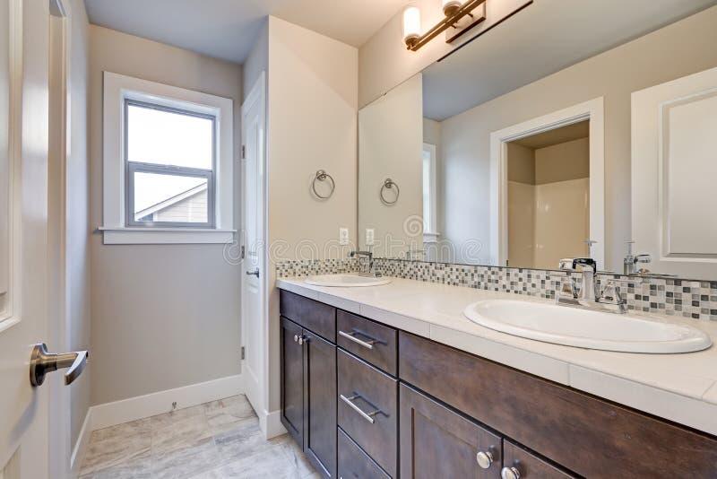 New light bathroom interior. With double sink dark wood bathroom vanity accented with mosaic backsplash. Northwest, USA stock photo