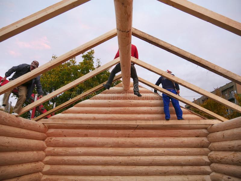 Carpenters assemble timber frame with common rafters on cabin roof royalty free stock photography