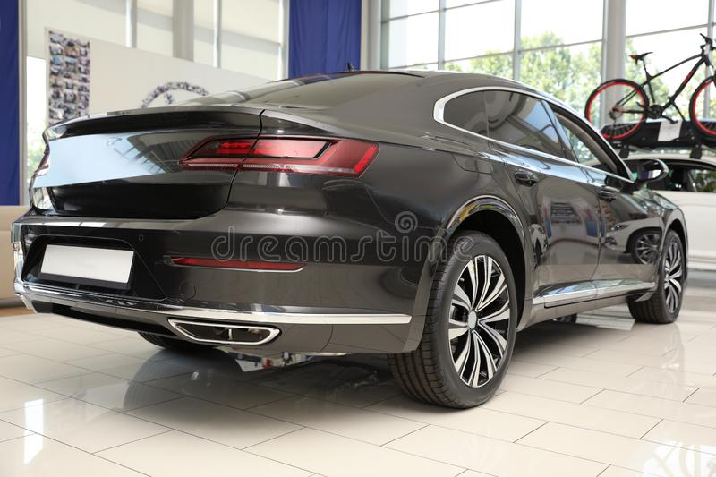 Luxury black car in modern auto dealership. New luxury black car in modern auto dealership stock photography