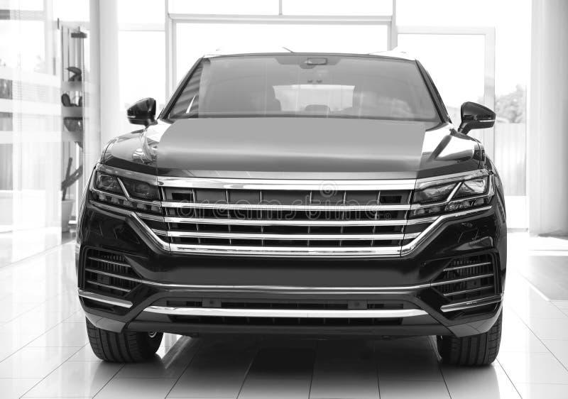 New luxury black car in auto dealership. New luxury black car in modern auto dealership stock images