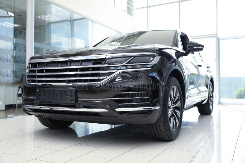 New luxury black car in auto dealership. New luxury black car in modern auto dealership royalty free stock photos