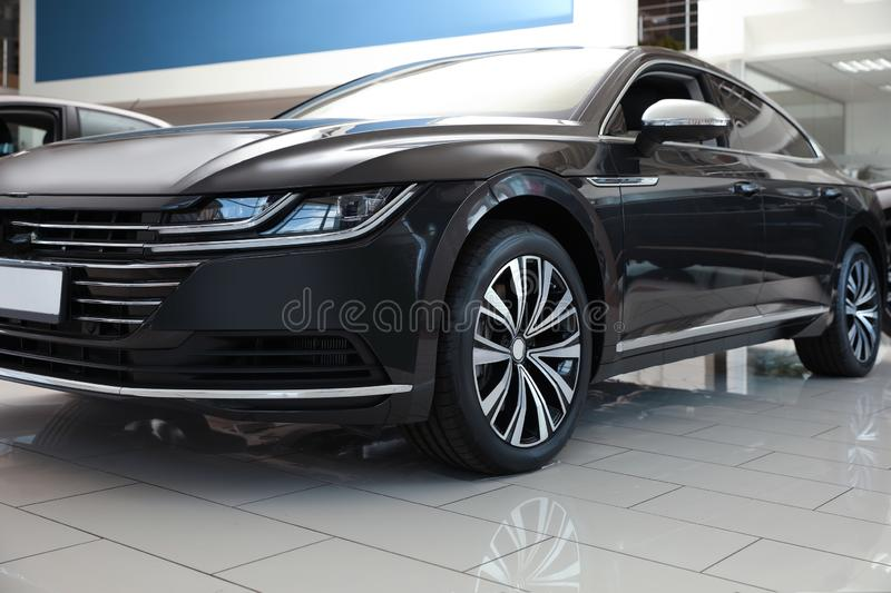 New luxury black car in modern auto dealership. Closeup royalty free stock photography