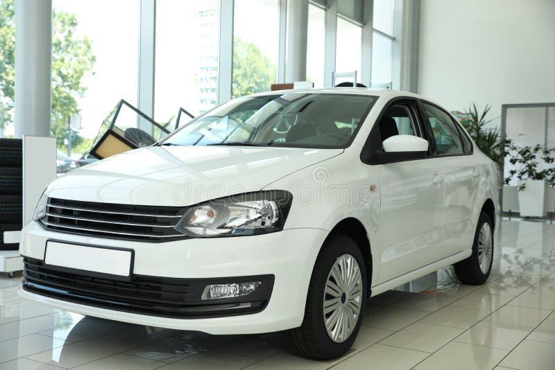 New luxury white car in  auto dealership. New luxury white car in modern auto dealership royalty free stock photo