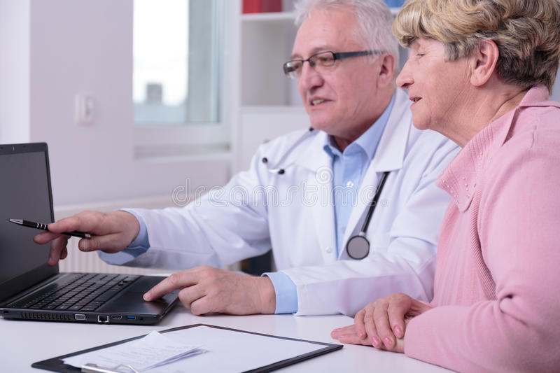 New medical treatment. Doctor is showing to his patient new medical treatment stock photography