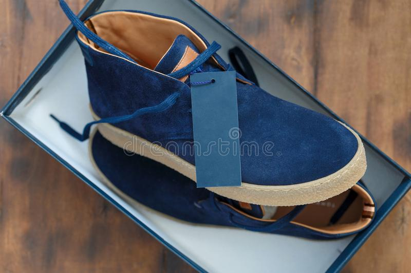 New mens shoes blank price tag label box sneakers. New mens shoes with blank price tag or label in a box. Male blue sneakers blank price tag or label close up in royalty free stock photos