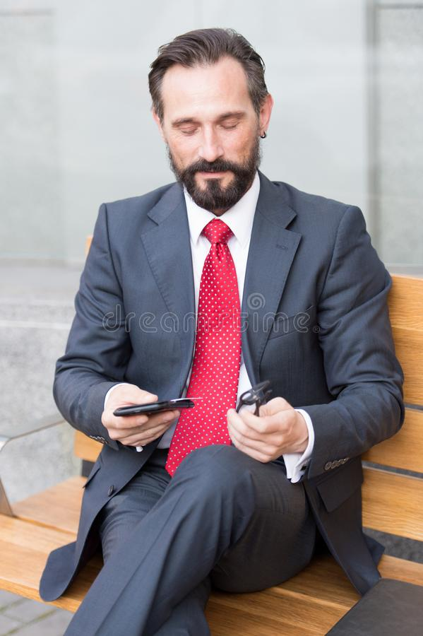 Positive middle aged manager using mobile phone while sitting outdoors royalty free stock photos