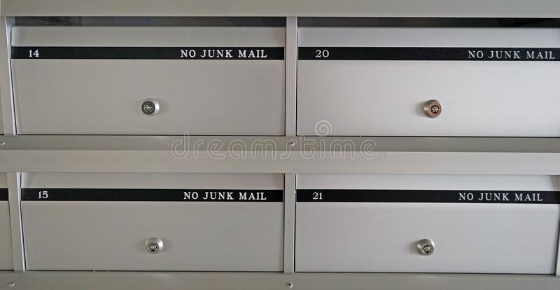 New metal mailboxes in an apartment building with flat numbers.  stock photos