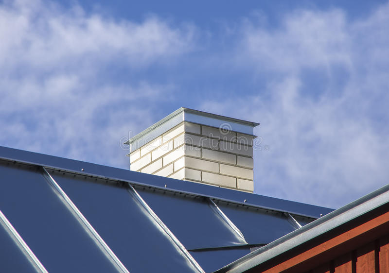 New metal roof with white chimney stock photography