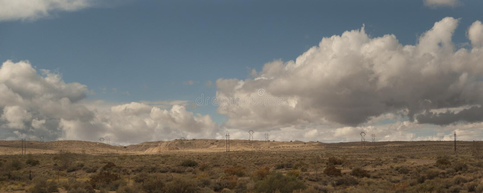 New Mexico landscape with power lines and clouds. Fair weather clouds in the autumn landscape of eastern New Mexico. Electric power lines cross the desert in a stock photography