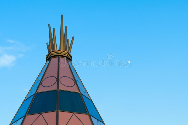 Giant indian teepee against big blue sky and small moon in background. New mexico native American teepee top with bright blue sky good for a banner or editorial royalty free stock image