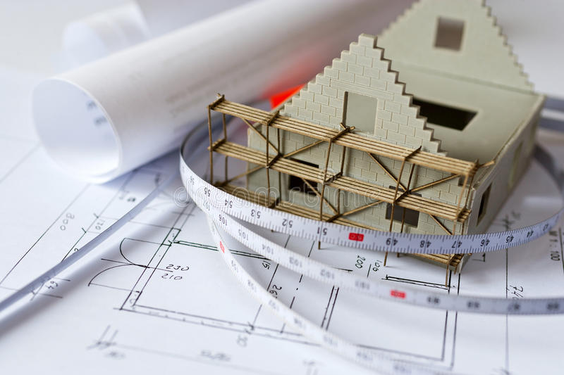 New model house on architecture blueprint plan at desk. New model house with scaffolding on architecture blueprint plan at desk - construction site royalty free stock photos