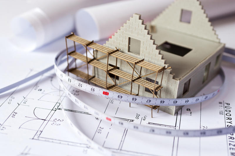 New model house with scaffolding on architecture blueprint plan. At desk - construction site royalty free stock photography