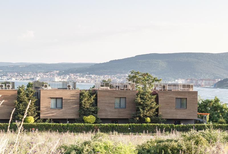 New modern architectural building terraced houses with flat roofs in a row, sea and mountains background stock images